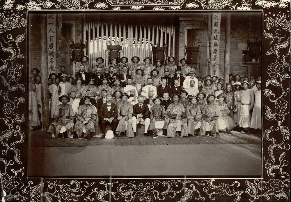 Photograph taken in Wuchang of a large group of British and Chinese men which includes the Viceroy and Governor, 30 July 1902. The photograph is annotated, 'Viceroy and Governor second row [from the back in the middle of the row sitting next to each other] sitting with Consular Body on right and left'. Reference: MS 15.6.3.023 QUB Special Collections and Archives